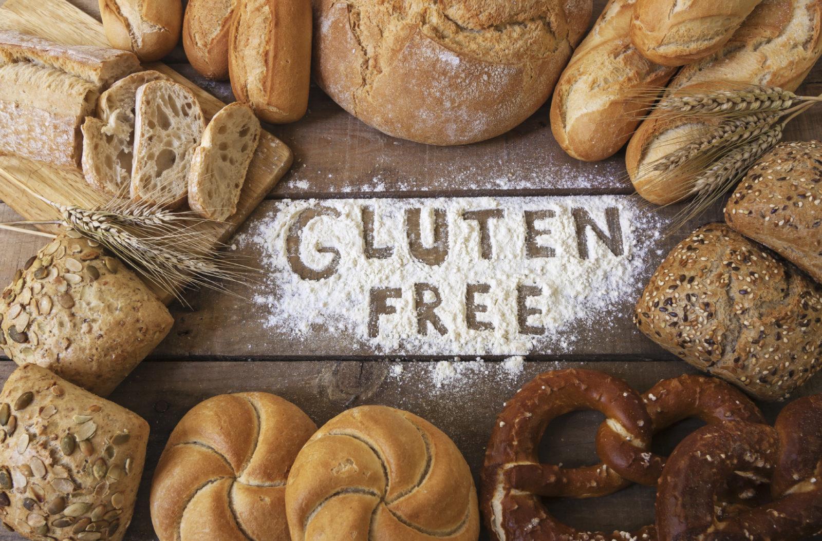 """Fotografia kolorowa. Na drewnianym stole, na środku zdjęcia rozsypano trochę białej mąki i wydrążono w niej napis """"gluten free"""". Naokoło poukładano różnego rodzaju pieczywo: chleb, bułki, precle itp. z różnego rodzaju mąki."""