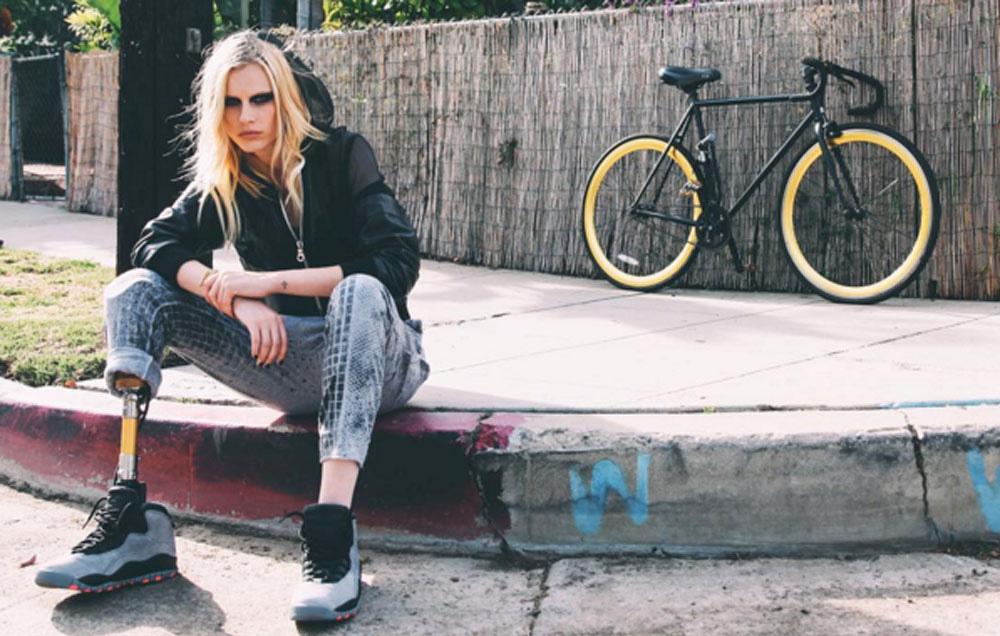 Dziewczyna z protezą nogi siedząca na krawężniku ubrana w jeansy i bluzę