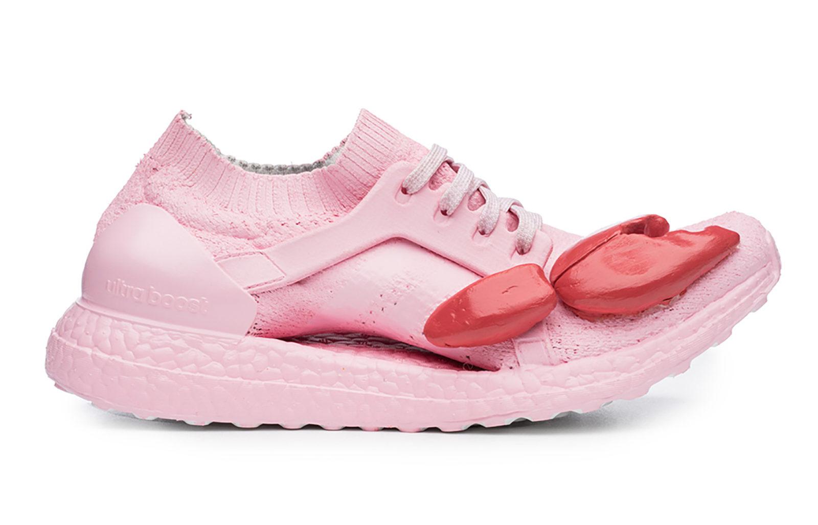 Fotografia reklamowa ukazując buty firmy Adidas, model Ultraboost w kolorze różowym z czerwonymi szczypcami homara na nosku buta.