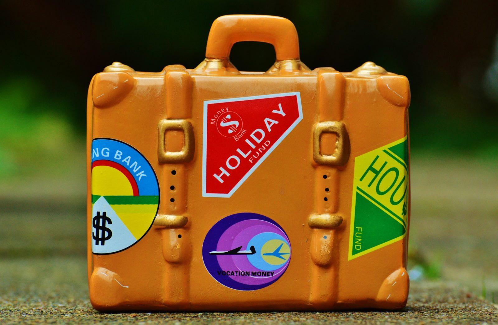 Pomarańczowa walizka z mnóstwem naklejek podróżnych