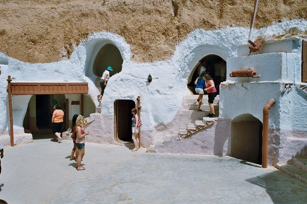 Grupa turystow, ktora zwiedza tunezyjskie miasteczko Matmata, w ktorym krecono Star Warsy. Widac ludzi wchodzących i wychodzacych z tamtejszych tuneli