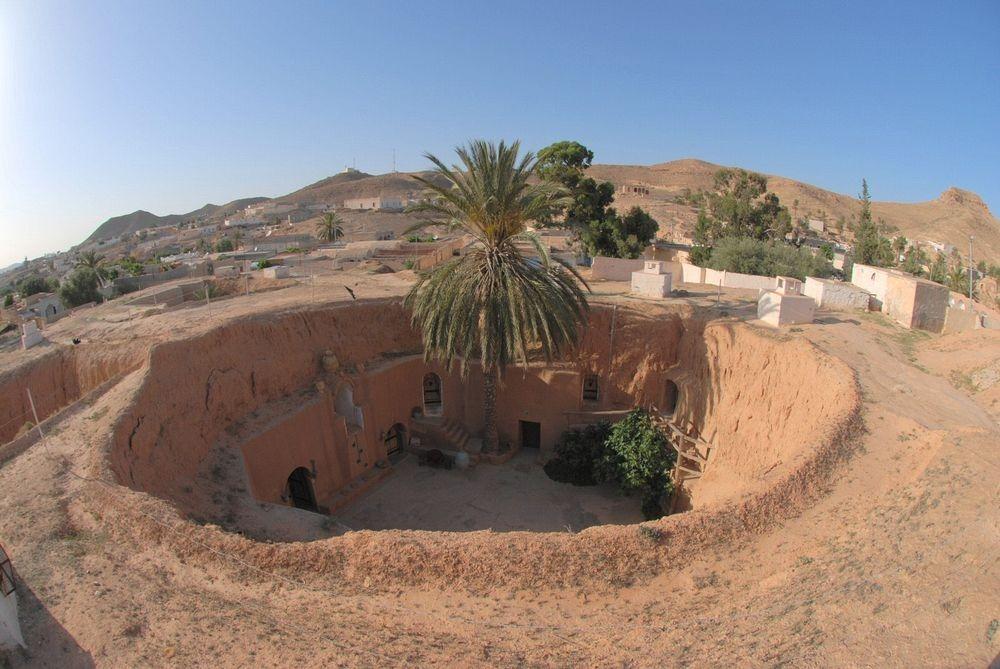 Na zdjęciu jest wioska Tunezyjska. W centralnym punkcie jest okrągły dziedziniec. W ścianach widać wydrążone tunele prowadzące do izb tubylcow