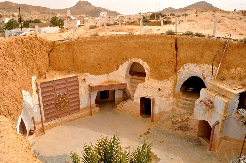 Zdjęcie tunezyjskiego miasteczka, ktore jest wydrążone w piaskowcu. Widać na środku dziedziniec i kilka różnych wejść do tuneli. Podobne osady mają bardzo dobre wlasciwosci izotermiczne. Latem pod ziemią jest chlodniej, a zimą daje ciepło.