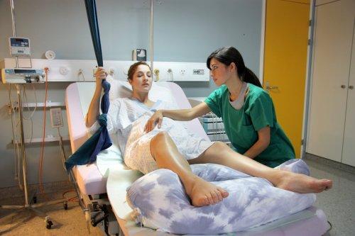 Kobieta w ciążu lezy na łożku, obok położna ubrana w zielony uniform uczy ją pozycji. Zdjecie z sali porodowej.