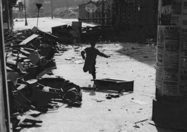 Powstaniec przebiegający pod osłoną barykady przez ul. Marszałkowską.