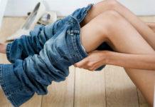 Fotografia kolororwa ukazująca damskie nogi. Kobieta siedzi i ubiera niebieskie jeansy. Jeansy wciągnięte są do połowy łydki.
