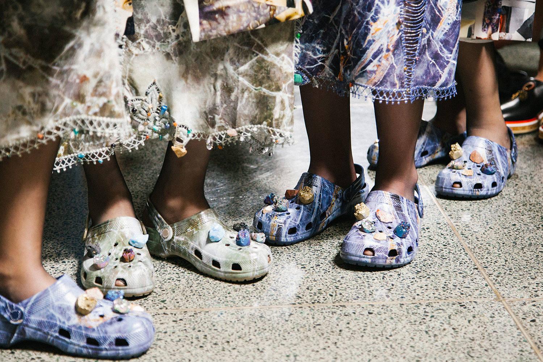 Ciemnoskóre nogi z założonymi Crocsami ozdobionymi kamykami