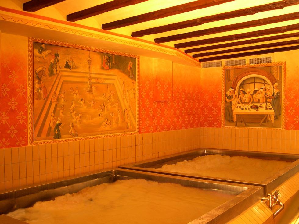 Zdjęcie dwoch basenów o rozm. 4x4m wypełnionych wodą oraz austriackim browarem Starkenberger. Na ścianach widać dodatkowo grafiki. Przeważa kolor pomarańczowy i żółty na zdjęciu.