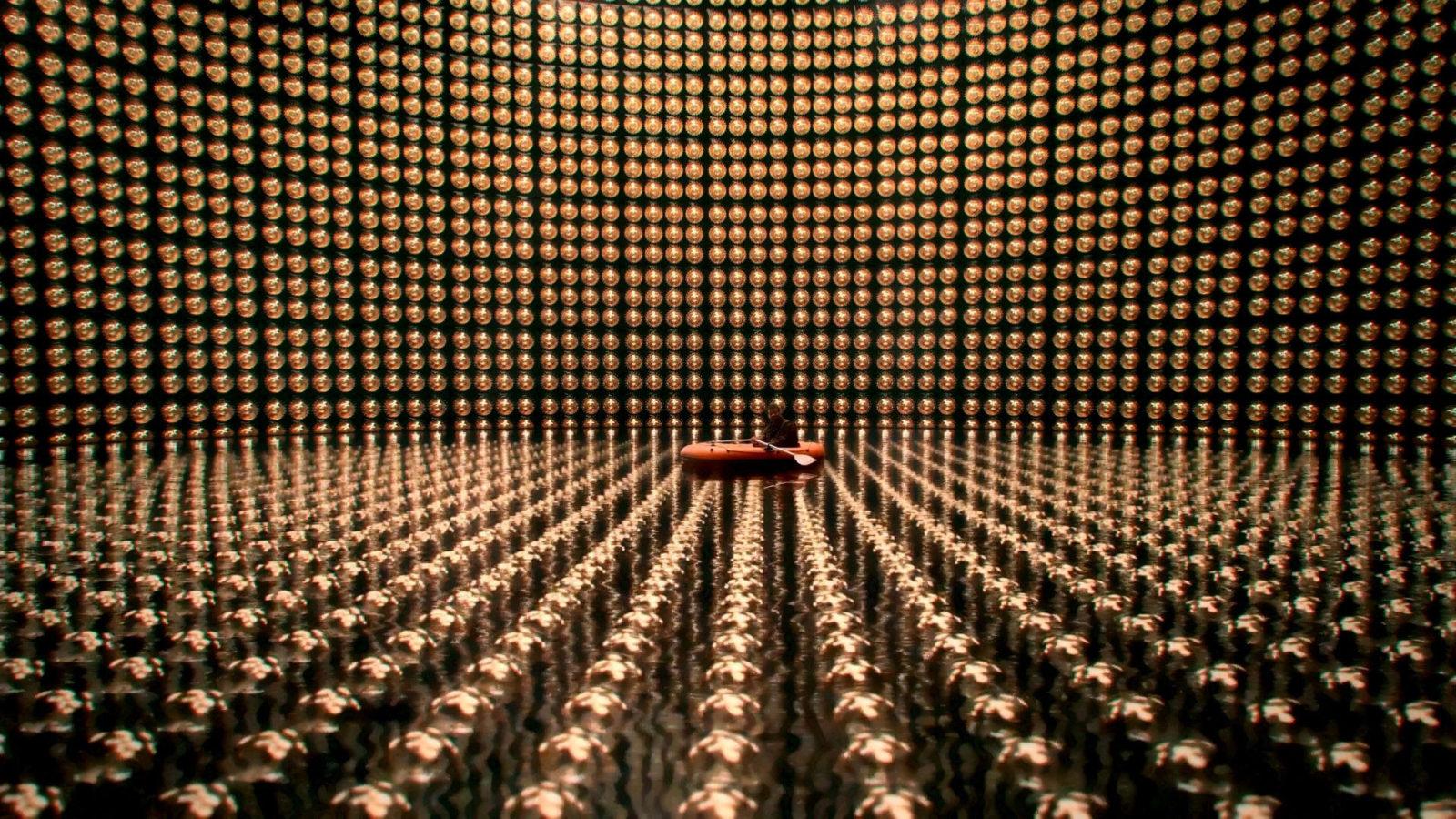 Super-Kamiokande w Japonii. Wielki detektor, ktory bardzo ciezko odiwedziec. Zbiornik wodny jakby wypełniony świecącymi się cząsteczkami. Widać gościa, któy pływa tam na pontonie.