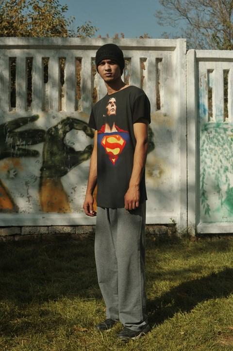 Zdjęcie młodego chłopaka, który jest ubrany w szary dres, czarną koszulkę z logo supermana. Stoi z rekoma wzdłuz tułowia. Ma czarne dłuższe włosy. Jest nieco ciemniejszej karnacji. Stoi na tle muru, na którym są różne bazgroły.