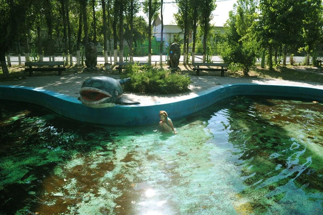 Zdjecie miejskiego basenu lub fontanny, miejsce specjalnie nie zadbane. Widać kucająca w wodzie osobę. W tle jest park, troche przyrody oraz ławką.