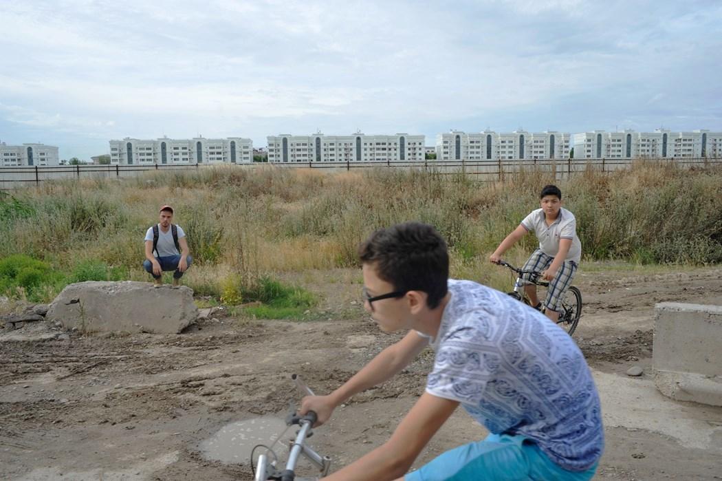 Zdjęcie opustoszałych terenów, gdzie dwóch chłopaków jezdzi na rowerach a trzeci pozuje do zdjęcia kucając na kamieniu.