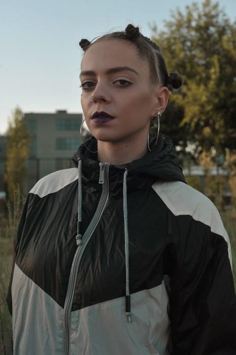 Dziewczyna ubrana w ortalionową kurtkę. Ma kolczyki, specyficzną, odważną fryzurę. W tle widać drzewo i blok.