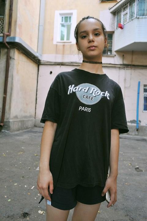 Dziewczyna stojąca na podwórku, ubrana w czarną koszulkę hardrock cafe. W tle widać budynek.