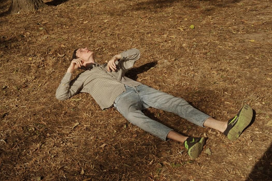 Chłopak lezący na ziemi. Ubrany w jasną koszulę w krate, jeansy, które podwijają mu się pod kolana.
