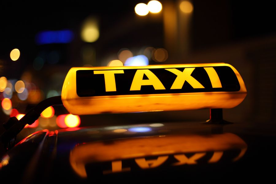 Zdjecie napisu taxi, który się świeci ze względu, że panuje już noc.