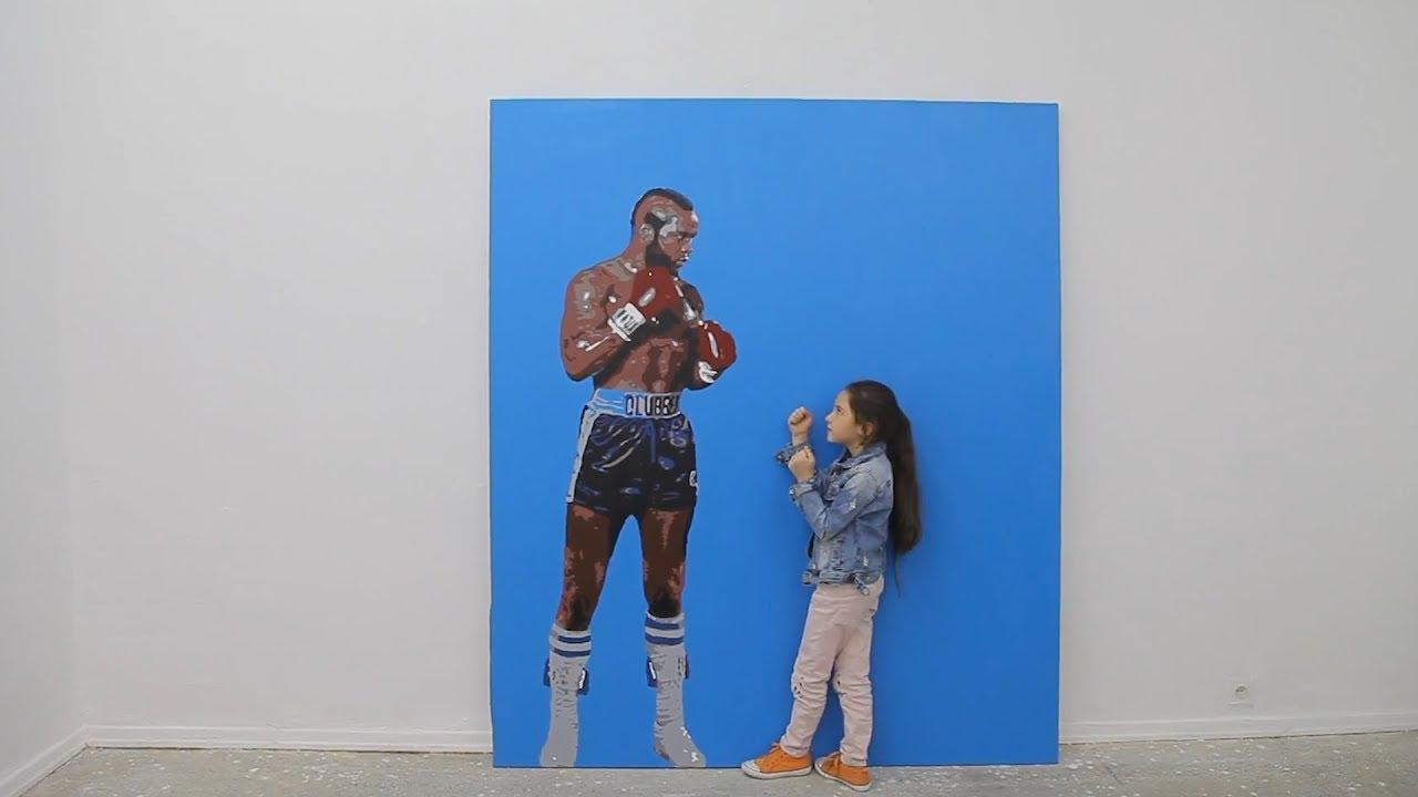 Obraz boksera czekajacego na walkę, uzupełniony przez dwa razy mniejsza dziewczynkę trzymająca gardę. Czarnoskory bokser namalowany jest na niebieskim tle. Dziewczynka ma na sobie jeansowa kurtkę, jasne spodnie i czarne włosy.