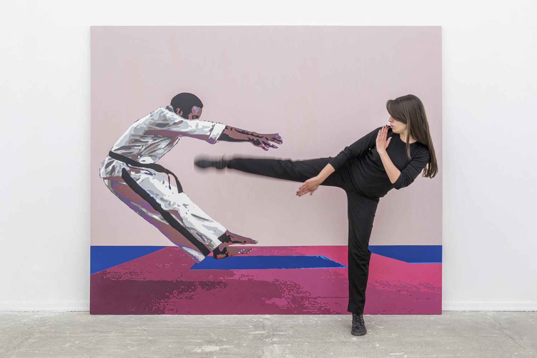 Karateka, ktory odlatuje jakby dostal nokautujący cios został namalowany na rozowym tle przez Tezi Gabunia. Ubrany jest w kimono. Do zdjecia pozuje dziewczyna ubrana na czarno, ktora wymierzyła mu właśnie kopniaka godnego Jean Claude Van Damme'a.