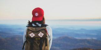 Dziewczyna siedzaca na krawędzi klifu w plecakiem na plecach, w czerwonej czapce z daszkiem