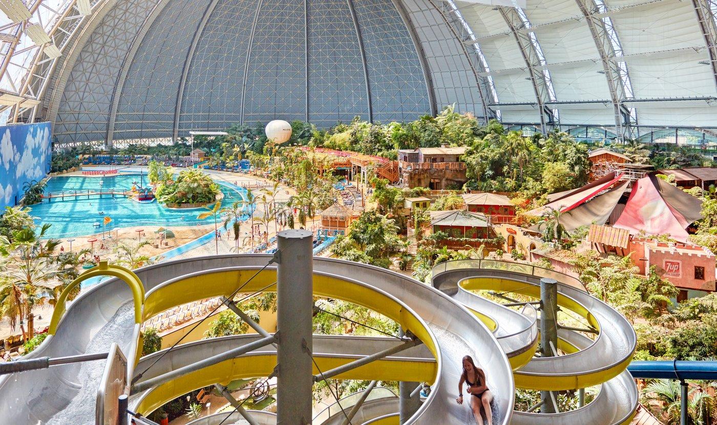 Zdjecie z Niemieckiego Aqua Parku, ktore przedstawia na pierwszym planie zjezdzalnie wodna na ktorej widac jedną osobe. W tle jest sztuczna plaża, kąpielisko, roslinnosc oraz domki