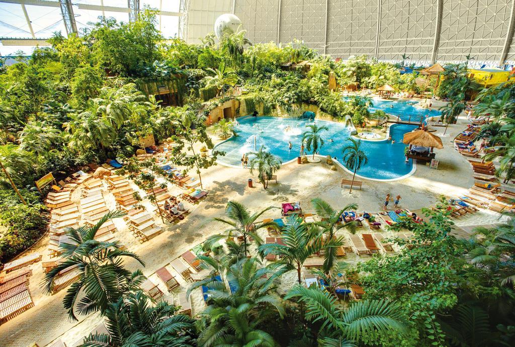 Zdjecie aqua parku z Niemiec. Widac roslinnosc, basen, lezaki.