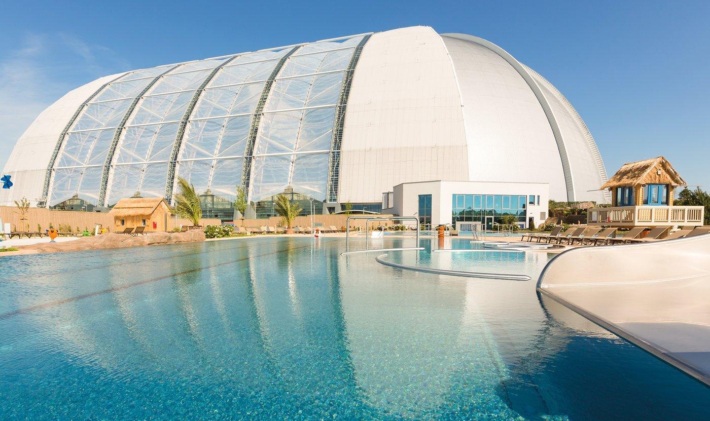 Zdjecie aquaparku niemieckiego od zewnatrz. Przed Halą jest ogromny basen oraz domki budowane na wzor hawajskich