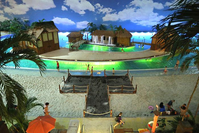 Niemiecki aquapark. Widac plaze oraz zrobione trzy domki na wodzie, ktore przypominają tropikalne chatki.