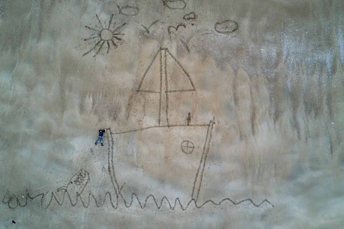 Zdjecie z lotu ptaka. Przedstawia duży rysunek wykonany na piasku. Widoczna jest łódka, słońce, ćwierkające ptaki, maszt, i jedna osoba, ktora w rzeczywistosci lezy na piasku, ale z tej perspektywy sprawia wrażenie wypadającej za burtę wprost w paszczę potwornego krakena, ktory rowniez jest narysowany na piasku.