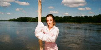 Dziewczyna w różowej spódnicy i białej bluzce stojąca nad brzegiem wody