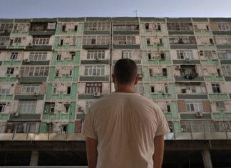 Chłopak stojący plecami do obiektywu w białej koszulce patrzy na stojący przed nim wysoki blok, który jest w kiepskim stanie. Wszystko tworzy ciekawy kontrast.