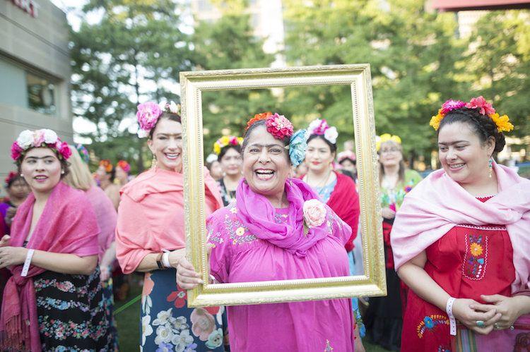 Kobieta trzymająca ramkę ubrana w różową chustę i kwiatowy wianek na głowie