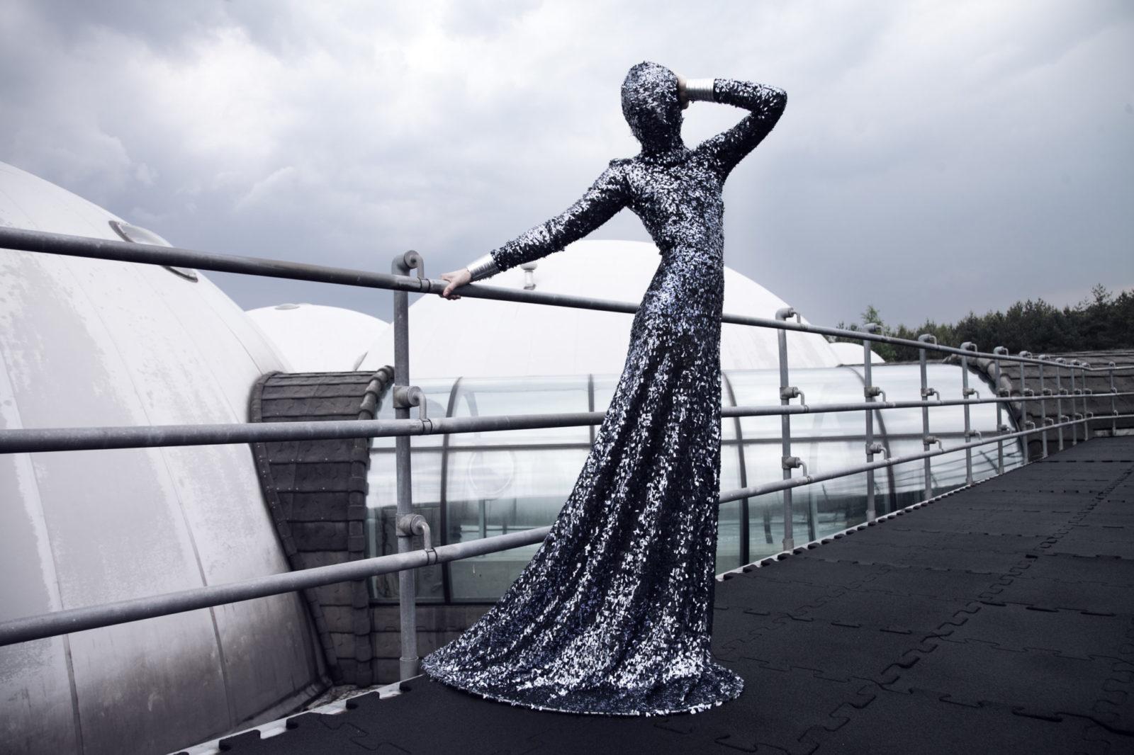 Kobieta trzymająca się za porczęcz stojąca w błyszczącej, ciemnej sukience z zakrytą twarzą