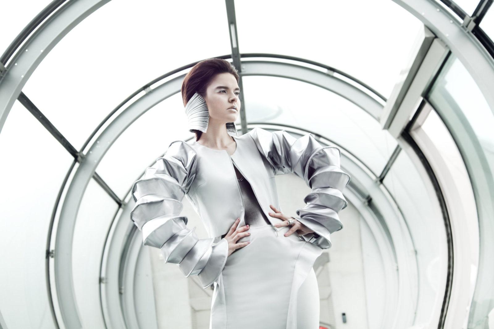 Rudowłosa dziewczyna trzymająca się za boki, stojąca w białej sukience z futurystycznymi elementami