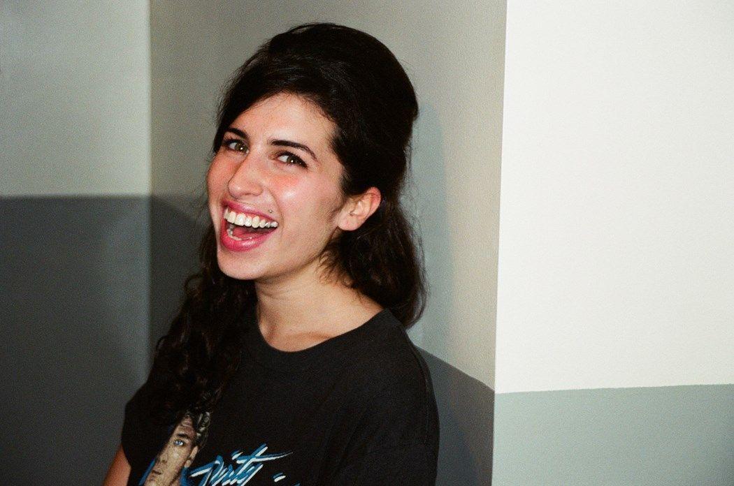 Uśmiechnięta czarnowłosa dziewczyna opierająca się o ścianę