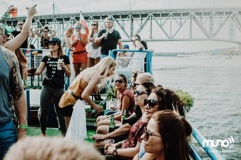 Grupa ludzi siedzących i stojących na płynącym statku