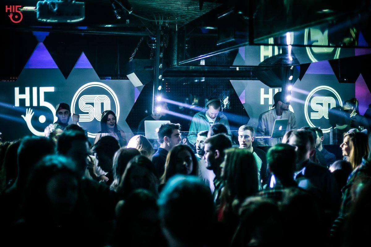 Ludzie bawiący się w klubie przy połyskujących laserach