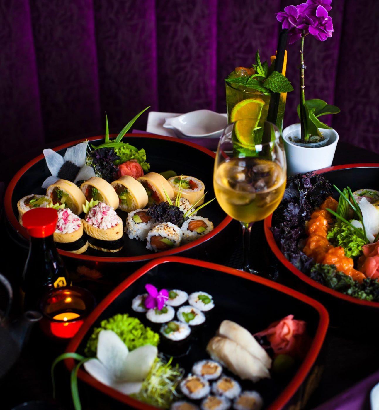 Sushi rozłożone na kilku talerzach, w tle fioletowa zasłona