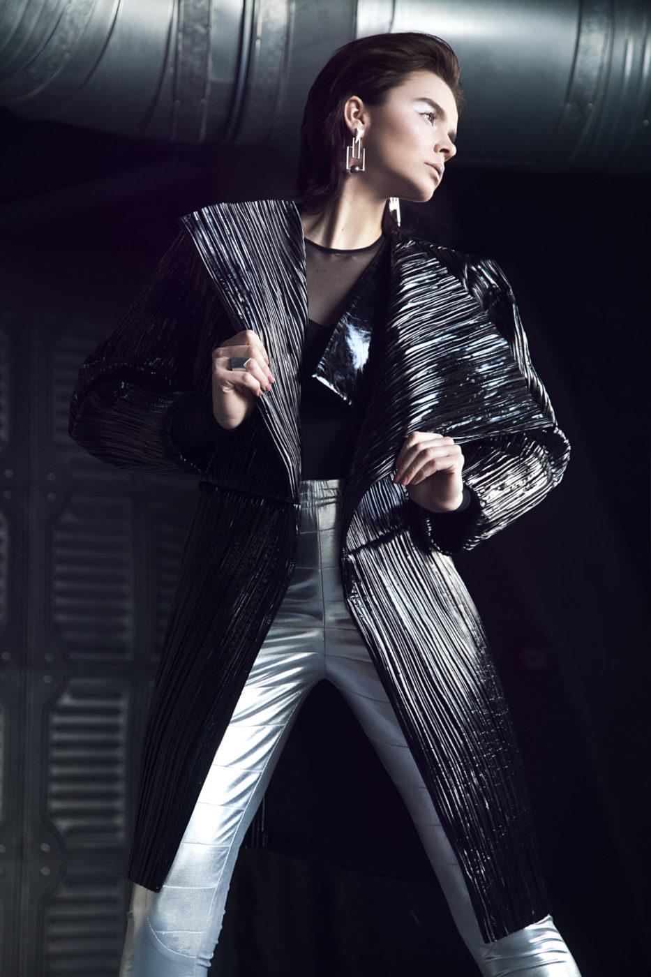 Kobieta stojąca w jasnych spodniach i ciemnym, futurystycznym płaszczu