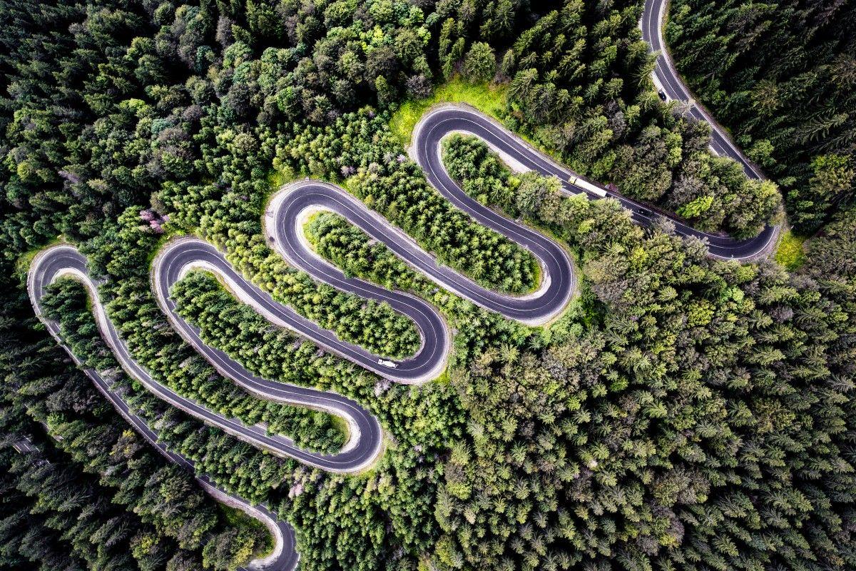 Zdjecie z lotu ptaka przedstawiajaca wijącą się jak wąż drogę asfaltową, która prowadzi to Transylwanii i bardzo kontrastuje wśród otaczającego ją lasu.