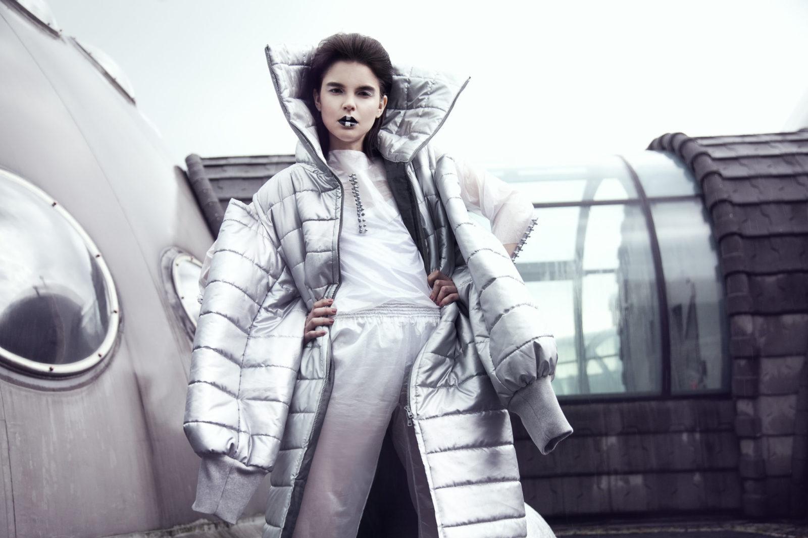 Kobieta trzymająca się za boki, stojąca w dużym, srebrnym płaszczu