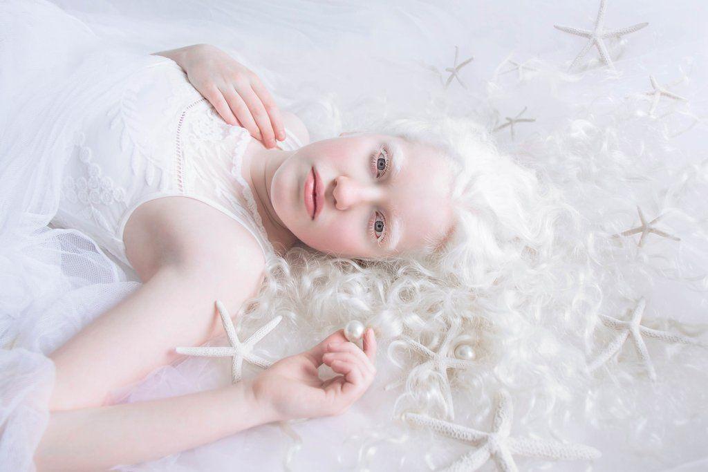 Fotografia kolorowa utrzymana w białych odcienaich. Na zdjęciu widać leżącą kobietę wśród białych rozgwiazd.
