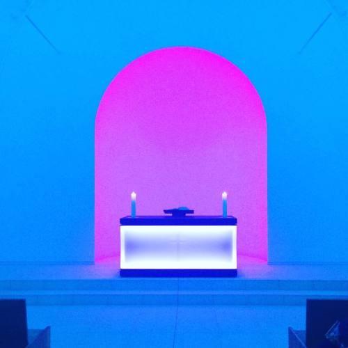 Kaplica podświetlona na niebiesko z różowym łukiem.