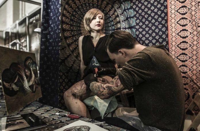 Kobieta siedząca na stołku i mężczyzna tatuujący jej nogę