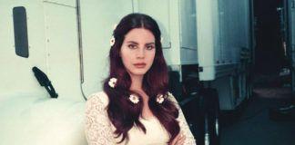 Uśmiechnięta dziewczyna w białej sukience, z rozpuszczonymi włosami i kwiatami w nich wplątanymi
