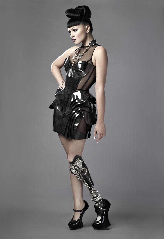 Dziewczyna ubrana w czarną sukienkę z elegancką protezą nogi