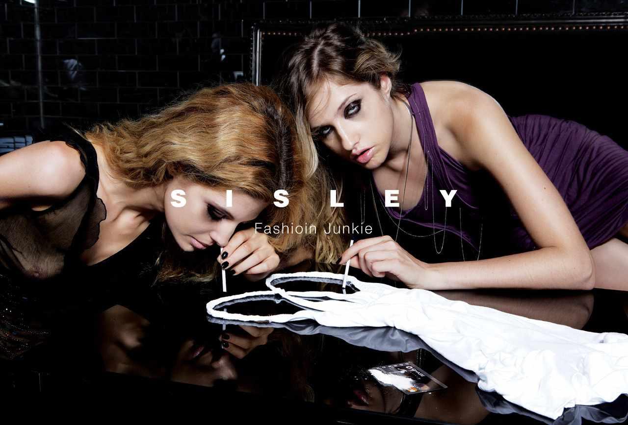 Fotografia reklamowa. Kampania marki Sisley pod tytułem Fashion Junkie. Na zdjęciu widać dwie modelki pochylające się nad stołem i wciągające rozłożoną białą sukienkę imitującą kokainę.