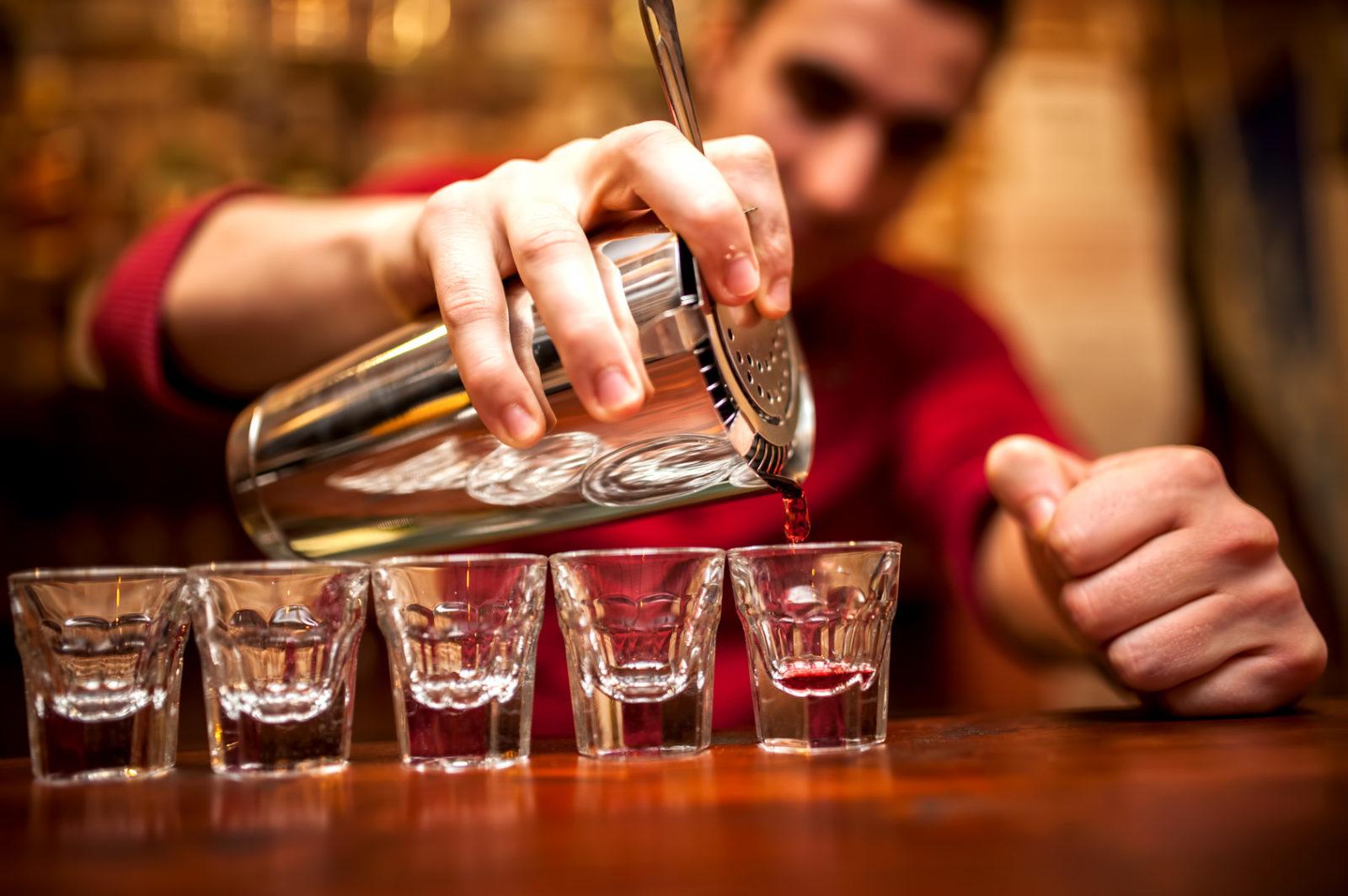 barman nalewa z shakera po kolei do kieliszków alkohol. W tle widac słabo wyostrzoną jego sylwetke. Ubrany jest w czerwoną koszulkę.