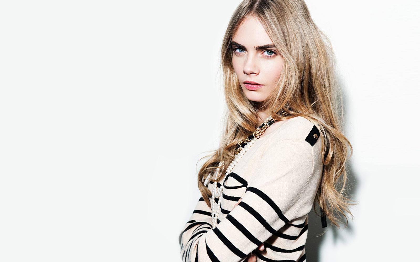 Kolorowa fotografia portretowa. Półprofilem stoi blondynka z długimi włosami. Ubrana jest w biały sweter w drobne czarne paski. Ma bardzo delikatny makijaż i zaakcentowane brwi.