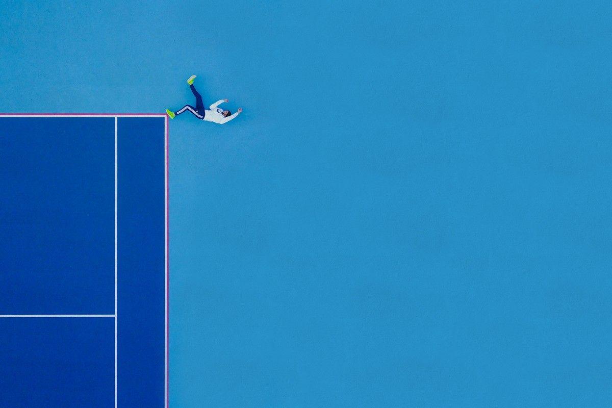 Zdjecie z lotu ptaka, ktore przedstawia boczną częśc boiska od tenisa i mezczyzne, ktory lezy na jego rogu. Wszystko razem tworzy jakby człowiek spadał z wysokosci. Boisko i tło dookoła boiska są niebieskie, mezczyzna ma na sobie białą bluzę