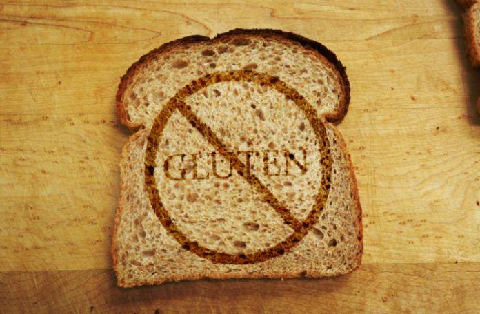 Fotografia kolorowa. Na drewnianym stole leży kromka chleba na której widać przekreślony napis